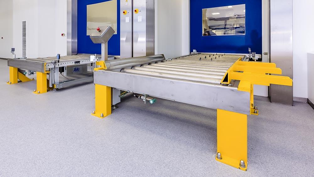 Die Rollenbahn hinter einem Schleusensytem mittels Schnellauftor und direktem Anschluss an Drehstationen zur Verteilung in das Lagersystem oder den Versand
