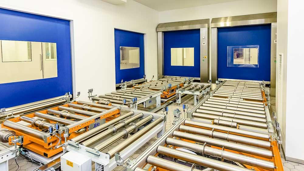 Die Rollenbahn hinter einem Schleusensytem mittels Schnellauftor und direktem Anschluss an Drehstationen zur Verteilung