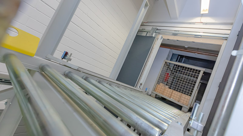 Gitterbox Transport über die Rollenbahn - Direkt aus dem Vertikalförderer auf die angetriebene Rollenbahn