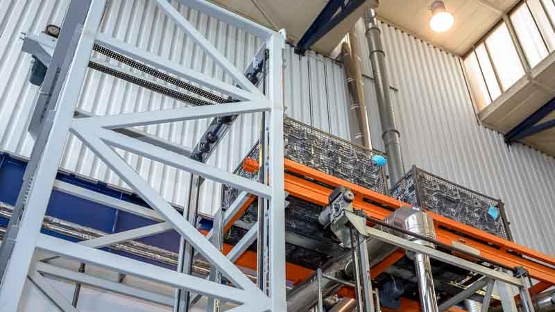 Optimale Raumausnutzung in der Produktionshalle durch den Vertikalförderer und Kettenförderer