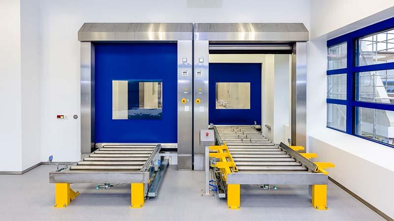 Rollenbahn Aufgabe und Abnahme in Verbindung mit einem Reinraum Schleusensystem - die Integration der Schnellauftore ist essentiell für die Wahrung der Schutzklasse
