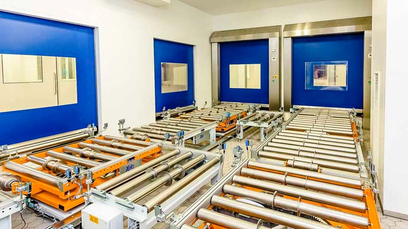 Rollenbahn im Systemverbund mit einer Reinraum Schleuse - die Schnellauftore sichern die Abschirmung des kritischen Bereich und laufen synchron mit der Förderanlage