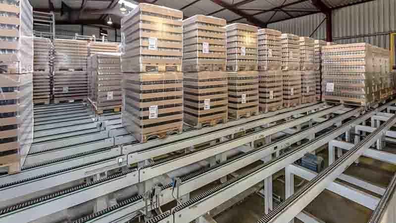 Kettenförderer für Fertigprodukte auf Europalette im Blockstau